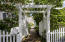 This lovely arbor leads the way into a lush and wooded backyard oasis.