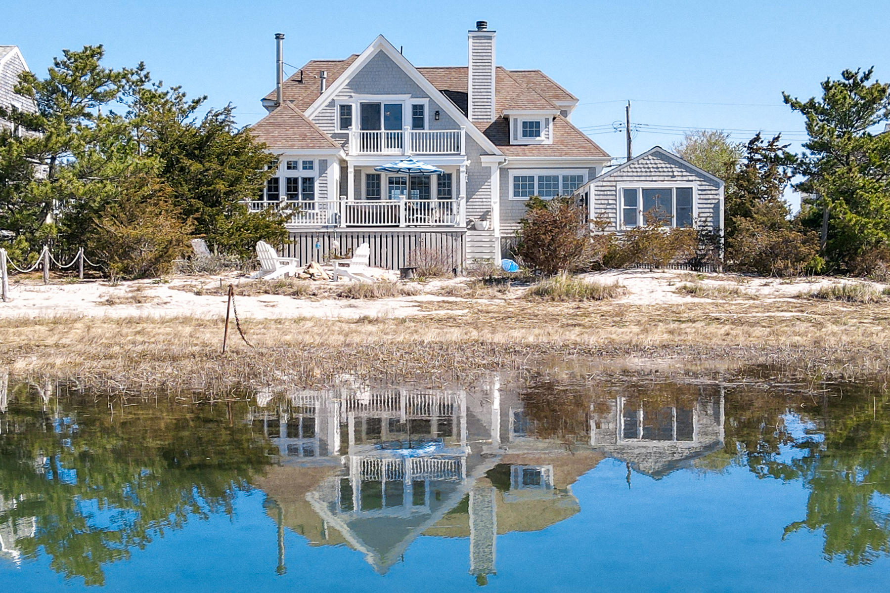 The best of both worlds in this charming seaside community has just arrived in time for summer! Many opportunities to own 2 year-round Scorton Creek marsh front houses just 50 yards to East Sandwich sandy ocean beach! Meander down the marsh path or anchor a small boat on the existing marsh mooring, enjoy the beach, then take in the sunsets and balmy evenings sitting on the back deck and by the fire pit making memories with friends and family. The 2008 quality custom-built main house offers many nice features including a 1st-floor sitting area and half bath ideal for a home office, wide pine/tile flooring throughout, granite/tile baths, gourmet kitchen/dining combo with granite counters, solid cabinets, high-end appliances and comes complete with its own special pizza oven direct from Italy! Relax by the fireplace in the living room while enjoying the marsh views, The 2nd level offers spectacular marsh views from the primary bedroom, with a beautifully designed private full bath, walk-in bonus room with laundry and stunning ocean views from the 2nd bedroom! The sweet guest cottage has marsh views, kitchenette, bathroom, outdoor shower and living/sleeping area. Great rental history!