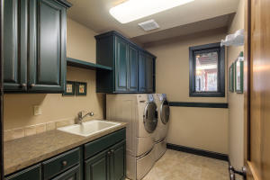 Lower level laundry room with sink, cabinets and plenty of storage