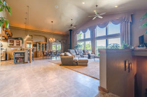 Very inviting great room with 16 foot vaulted ceilings with stunning windows looking out above the tree tops! Custom made drapery and remote blinds