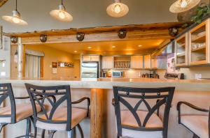 Carved bears accent the wood beams above breakfast bar area, and pendant lighting accents compliment overall theme nicely