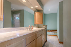 Plenty of counter space and cabinets for storage in master bathroom suite