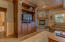 Is revealed in the built-in entertainment center and stone fireplace.