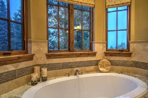 Oversized Bain Ultra Jacuzzi tub with granite surround, Borghese Walker Zanger tile accents.