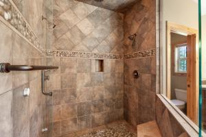 Three shower heads, one rain influenced, steam shower, tile with stone details, glass doors