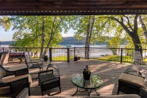 88 feet of prime waterfront in Rockford Bay on Lake Coeur d Alene. Huge newer entertainers deck, canopied tree cover, level lawn to SANDY BEACH to waters edge and your dock....