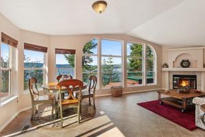 Inviting living room and dining area with wood burning fireplace and picture windows capturing the expansive lake views.