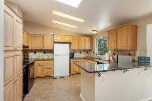 Spacious kitchen with granite counters and tile floors.
