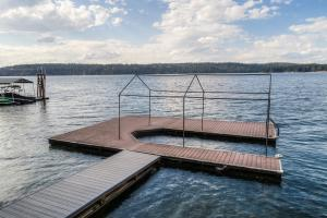 Log dock with composite decking and covered U-shaped boat slip.