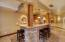 Wet bar with space for friends to gather with stone pillars and bar seating, mini fridge