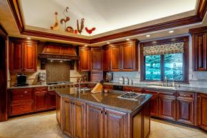 Travertine backsplash, Eat-in breakfast area, Custom built-in Sub Zero refrigerator, 2 refrigerator doors in cabinets, Built in microwave, Island with double burner, Prep sink, Wolfe double wall oven, 2 dishwashers (one Bosch) - all with the chef in mind!