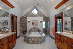 Your own private Spa-like Master En-suite with central jetted tub encased in granite, dual walk-in shower with rain showerheads, and his & her vanities with granite, granite flooring with hydronic heat - You'll want to linger and lounge!