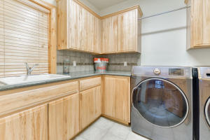 Laundry room with big sink and ample storage.