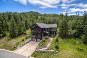 Golf course and mountain views in front and behind this home set among the trees with a rustic style.