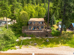 100 feet of waterfront and L-Shaped Dock. Grass and sand area off decks. Easy access to Dock