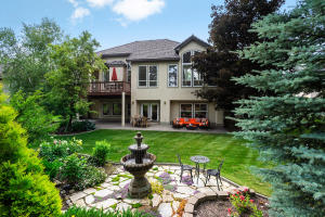 Gorgeous inside and out with every detail dripping with elegance. A view of the back of the home with fountain, manicured lawns and mature landscaping