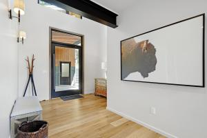 Bright and open entry way connects to the garage via breezeway and large scale glass pivot door.