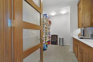 Walk-in butler's pantry with sink and built in cabinets, storage wall and second laundry hook-up.
