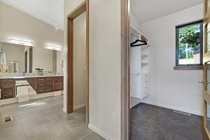 Walk-in closet with built in storage, toilet-closet and dual sinks set in floating quartz counter with under cabinet lighting. The spacious, fully tiled shower is right around the corner.