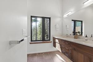 A large window overlooking the forest lets tons of natural light spill in to your master bathroom.