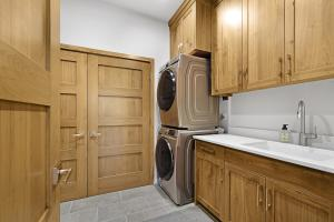 Large laundry room with sink, tons of cabinetry, under stair storage space and utility closet with two hot water tanks.