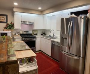 Kitchen with brand new stainless steel appliances. Gas range has center grill.