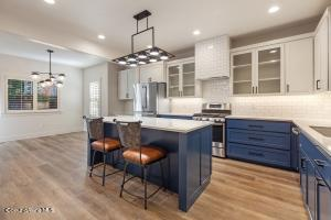 Breakfast island, seeded glass cabinet doors, lots of counter space, custom lighting makes this spacious kitchen the center of activities