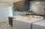 Laundry room with sink, tile backsplash and tile floors.