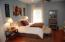 Large bedroom in the in-law suite with wood floors and a sitting room.