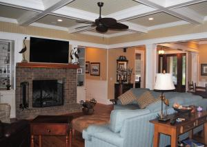 Coffered ceilings and brick hearth fireplace in the living room.