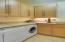 Laundry room with undercounter washer/dryer, sink, and broom closet