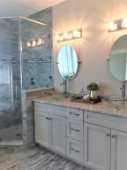 Polished and Sleek Double Vanity Cabinet with Quartz Counter Tops, and Oval Floating Mirrors