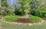 This backyard boasts a beautiful pond, mature trees, and irrigation!