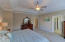 Spacious master bedroom features crown molding and tray ceiling