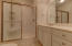 The master bath offers a tile floor and a wide walk in shower with bench seat.