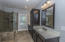 Large master bathroom with dual sinks, tile flooring and luxury tile surround stand-up shower.