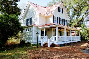 Front elevation of this charming lake house with red metal roof