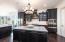 White backsplash accents black cabinetry and quartz counter tops .
