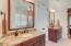 Framed mirrors, bronzed-colored fixtures on raised granite countertop vanities