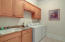 Full-sized laundry room with plenty of storage and utility sink