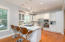Kitchen features bar seating with designer pendant lighting.