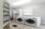 Laundry room has utility sink along with loads of shelving