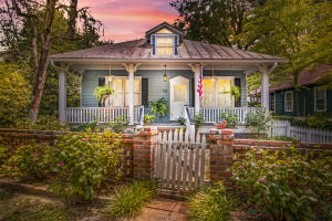 """If you've been waiting for a home with character & charm, your chance has finally arrived. But move quickly or this shotgun-style Carolina Cottage will be gone in a flash! This adorable historic home in the HEART of downtown Summerville has SO MUCH to offer; it has been fully & lovingly remodeled & is move-in ready. The kitchen & master bath were completely gutted & redone, wood floors refinished (new floors in kitchen), new HVAC & ductwork, new tankless gas heater with ionizer, new gutters & so much more! Located adjacent to the historic Squirrel Inn, this 1910 build is perfectly placed for the most ''walkable'' small-town living possible. You're steps from Azalea Park & its tennis courts & moments from the shops & restaurants of Short Central & Hutchinson Square. Book your showing ASAP!  This home also features a newer, well-built detached garage with 2-car carport. The garage features an over-sized 1.5-car enclosed garage that's actually plumbed for a half bath! The building has its own power with a 220 Amp electrical box. Also of note, the ceiling joists are 18"""" and reportedly built with the strength to carry a 2nd floor.  This property is high & dry as the dry-as-a-bone crawl space will attest to. Not to mention that it is in a minimal flood zone that does not require flood insurance AND it is a No-Evacuation Zone for added peace & comfort.  The work done on this home has been extensive! It truly is one-of-a-kind and ready for you to downsize in the middle of the action or start your family in style.  All of the improvements described below were performed between December 2017 and March 2019  - Installed high-end Rinnai Tankless Hot Water Heater with ionization feature that makes it self-cleaning & never needs flushing, removes scale buildup & provides cleaners dishes & clothes. - HVAC (installed brand new Trane HVAC including replacement of all vents/ducts 1st and 2nd floor Dec 2017)  Outside - Railings on front brick steps - Installed rain gutters across fron"""