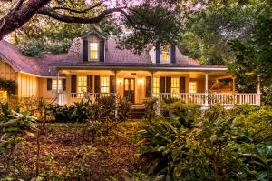 "This one-of-a-kind home in historic Summerville is the perfect blend of vintage charm & modern comfort. A wide SOUTHERN porch wraps around the front & side of the home, complete with wicker swing & garden views. Enter the front of the home through a custom mahogany front door. Once inside, you'll find lovely, large stone flooring in the foyer. The formal living room, dining room & family room boast beautiful 10'' heart pine floors. The family room has a custom wood ceiling & a grand brick gas fireplace. The kitchen features GRANITE COUNTERS & an eat-in area. The first floor Master Suite includes a Master bath with dual vanities and a recently renovated shower with custom large tile. Upstairs you'll find two bedrooms, a full bathroom, & ample storage space as well. The rear of the home has a spacious screened in deck equipped with plenty of entertaining space. The backyard is a gardener's paradise. Outside you'll find a koi pond and multiple flower / plant beds, a huge LIVE OAK tree shading the back yard, and many other planting nooks and crannies for your ""garden angel"" to fill. This home has recently had the entire crawl space renovated and encapsulated.  Be prepared to spend some time being delighted as you explore this lovely Summerville cottage."