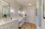 Owners bathroom with dual vanities, dressing area, shower with rain head and bench