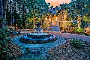 Tucked away on a large and private wooded lot, behind a stately gated entrance at the end of an elegant brick paver driveway, you'll find this breathtaking example of Lowcountry charm. Opulent and meticulously maintained, this stunning custom home is nestled amid lush tropical landscaping on 2.75 acres of land. The driveway encircles a custom estate fountain directly in front of the home, while a wide and welcoming staircase leads up to a large rocking chair style front porch. A heavy front door, featuring a beautiful leaded glass oval lite and flanked by matching leaded glass sidelights, opens into the arched and columned foyer, where coffered ceilings, gleaming hardwood floors, and crisp white crown molding draw you into the meticulously-crafted living space. To the right of the entryway is an elegant formal dining room, where a deep tray ceiling, attractive chair rails and crown molding, and a classic chandelier add an air of sophistication and refinement to any occasion, whether you're hosting a family gathering or entertaining friends. You'll love the great room, where the lofty vaulted ceiling and suspended beam create a bright open space, while the large gas fireplace calls to mind cozy evenings spent with loved ones in front of a flickering fire. The large gourmet-style kitchen features recessed lighting, set into a gorgeous coffered ceiling, and is equipped with high-end stainless steel appliances (including a wall oven and Dacor 6-burner gas cooktop and ventilation hood), handsome polished granite countertops, raised panel Cherry cabinets, a stainless steel farmhouse sink, a raised breakfast bar, and abundance of cabinet and counter space, and a pantry for additional storage space. Also on the main floor are two sizable guest bedrooms and a full bathroom with a wide vanity and tub/shower combo. Between the guest rooms, a glass paned center-hinged door opens onto a wide screened porch, perfect for unwinding under the ceiling fan with a cool drink after a lo