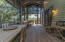 An enormous screened porch, 12'x25', with soaring ceilings, transitioning to the gardens and lakeside terraces