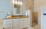 Master bathroom features his & her vanity with granite countertops, updated lighting and mirrors!