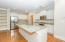Gourmet kitchen boasts an oversized island with granite countertops, beautiful white cabinetry, stainless appliances, tile backsplash, and recessed lighting.