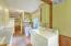 A genuine Mud/Laundry Room with brick flooring, folding bar, wall of cabinetry & half bath.